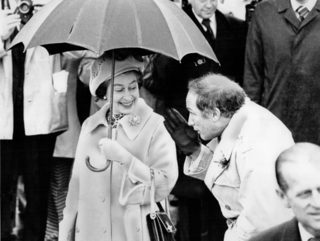 Queen Elizabeth and Prime Minister Pierre Trudeau share an umbrella