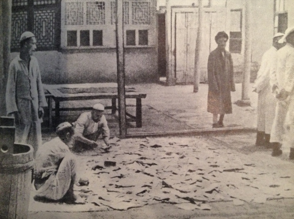 From 'The land of Khotan' by H.W. Bailey. This photograph of the Mint in Khotan shows newly printed banknotes spread out on the ground to dry in the sun before being put into use.
