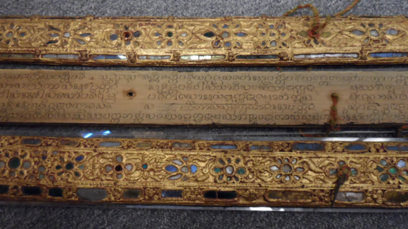 Kammavāca palm leaf manuscript from Laos. It has wooden covers which are decorated with lacquer, gilt and mirror glass inlay. British Library, Or.11797