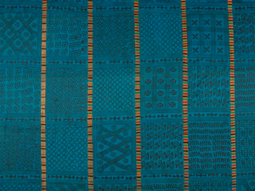 Section of a hand-stamped textile on display in the West Africa: Word, Symbol, Song exhibition, showing adinkra symbols from Ghana. Some panels show the King's symbol (adinkrahene) composed of three concentric circles, signifying leadership and greatness. Ghana, 1960s. British Library.