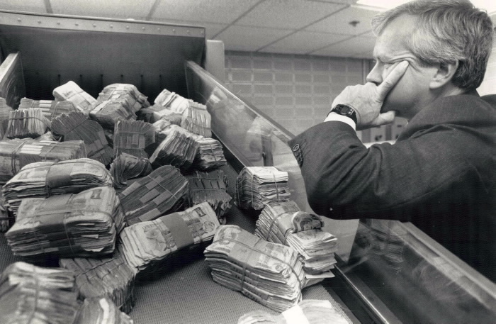 Doomed dollars: The Bank of Canada used to burn old bills that were too scruffy to be recirculated. Today; the millions are shredded into specks of paper by this machine; under the watchful eye of Ross Tousaw; Toronto agent and banking operations adviser for the central bank.