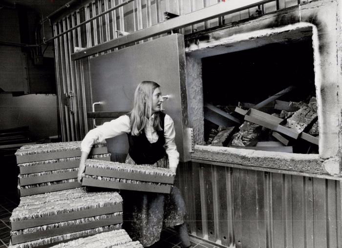 Vicki Hodgson stokes bank furnace with used bills