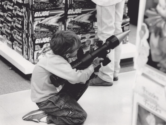 Boy crunches down and looks through the sights ofa toy rocket launcher
