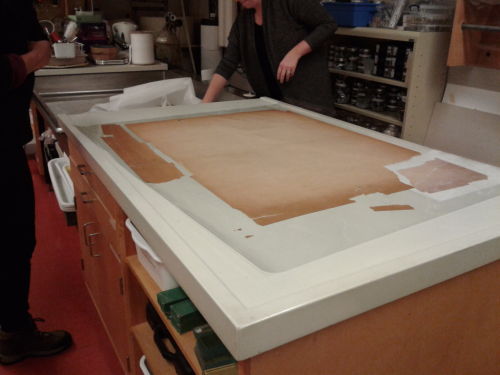 Larger poster with multiple detached pieces on table in conservation lab