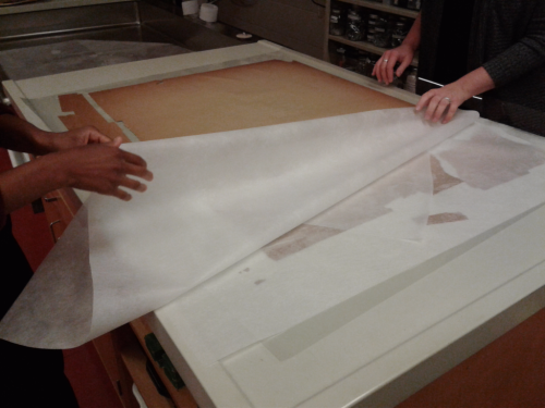 Transparent paper being pulled by two sheets of hands to reveal a brown poster
